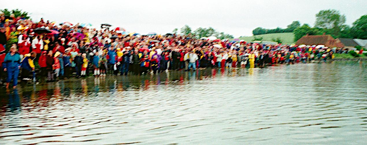 Mange mennesker på en smal strandbred.