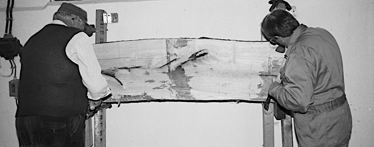 En planke bliver hugget ren til den rette tykkelse.